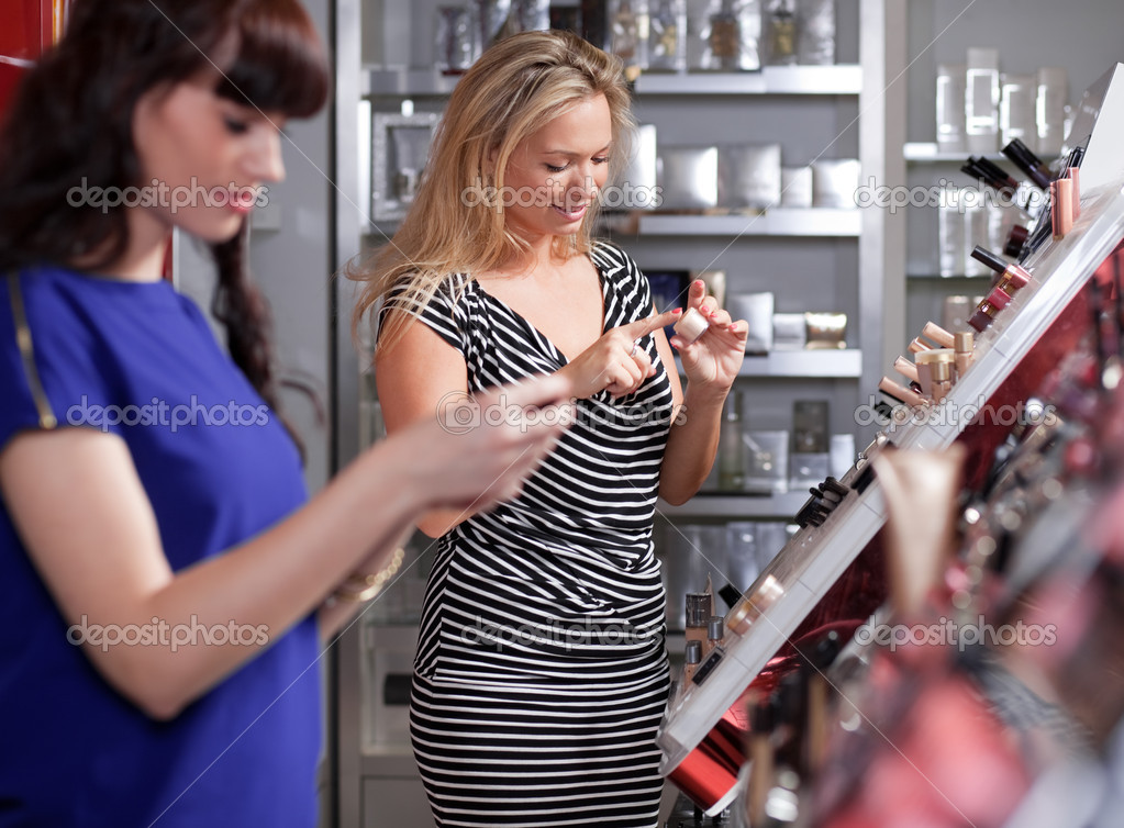 Girlfriends buying and testing cosmetics in a beauty store  Stock Photo #9813974