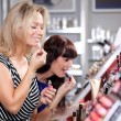 Women buying and testing cosmetics — Stock Photo