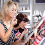 Women buying and testing cosmetics — Stock Photo