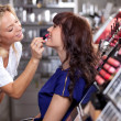 Make up artist applying lipstick to a customer in a beauty store — Stock Photo