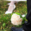 Stock Photo: Bridal bouquet of roses with bride and groom