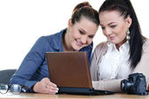 Two girls photographer looking for a netbook photos — Stock Photo