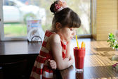 Child girl drinking strawberry smoothie — Stock Photo