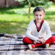 Child girl sitting on plaid in a garden — Stock Photo