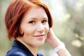 Closeup portrait of beautiful woman with red hair — Stock Photo