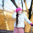Little girl wearing pink cap with a scooter — Stock Photo #7963352