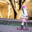 Little girl wearing pink cap with a scooter — Stock Photo #7963360