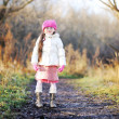 Little girl wearing pink cap walks along the road — Stock Photo