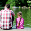 Stock Photo: Young father and his daughter near pond