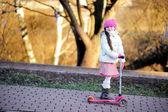 Klein meisje dragen van roze pet met een scooter — Stockfoto