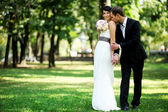 Bride and groom posing outdoors on wedding day — Photo