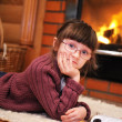 Portrait of a child girl in front of fireplace — Stock Photo