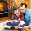 Royalty-Free Stock Photo: Father and daughter reading in front of fireplace