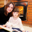 Mother and daughter sitting in front of fireplace - Stockfoto