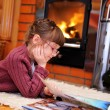 Child girl is reading in front of fireplace — Stock Photo