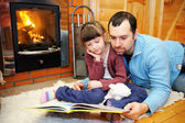 Father and daughter reading in front of fireplace — Stock Photo