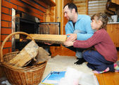 Father and daughter putting wood into fireplace — Stock Photo