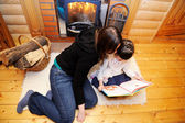 Mother and daughter reading in front of fireplace — Stock Photo