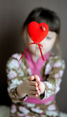 Heart shaped toy with ladybird in child's hands — Stock Photo