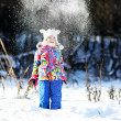Toddler girl in colorful snowsuit plays in snow — Stock Photo