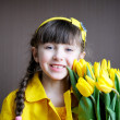 Sunny child girl with bouquet of yellow tulips — Stock Photo #9034707