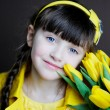 Sunny child girl with bouquet of yellow tulips — Stock Photo #9034718