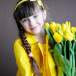 Sunny child girl with bouquet of yellow tulips - Stock Photo