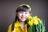 Menina criança ensolarado com buquê de tulipas amarelas — Fotografia Stock
