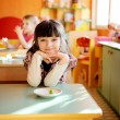 Happy little girl sitting at a table — Stock Photo #9450147