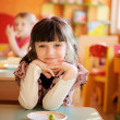 Happy little girl sitting at a table — Stock Photo #9450151
