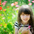 Smiling little girl sitting on poppy field — Stock Photo #9450177
