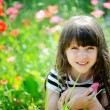 Smiling little girl sitting on poppy field — Stock Photo
