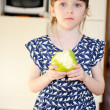 Adorable child girl eating apple at home — Stock Photo