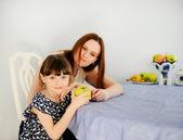 Jeune maman avec sa petite fille dans la cuisine — Photo