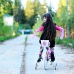 Fancy little girl riding her pink bike — Stock Photo