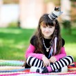 Beauty little princess sitting outdoors on blanket — Stock Photo