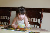 Little girl drinking tea indoors at a table — Stock Photo
