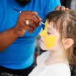 Cute little girl has her face painted — Stock Photo
