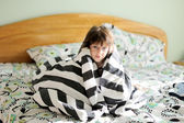 Sad child girl wrapped in blanket — Stock Photo