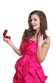 Beautiful girl in cocktail dress opening a gift — Stock Photo