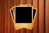 Blank instant photo frames on old wooden background. — Stockfoto