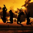 Stock Photo: Silhouette of friends jumping in sunset