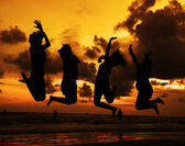 Silhouette of friends jumping in sunset — Stock Photo