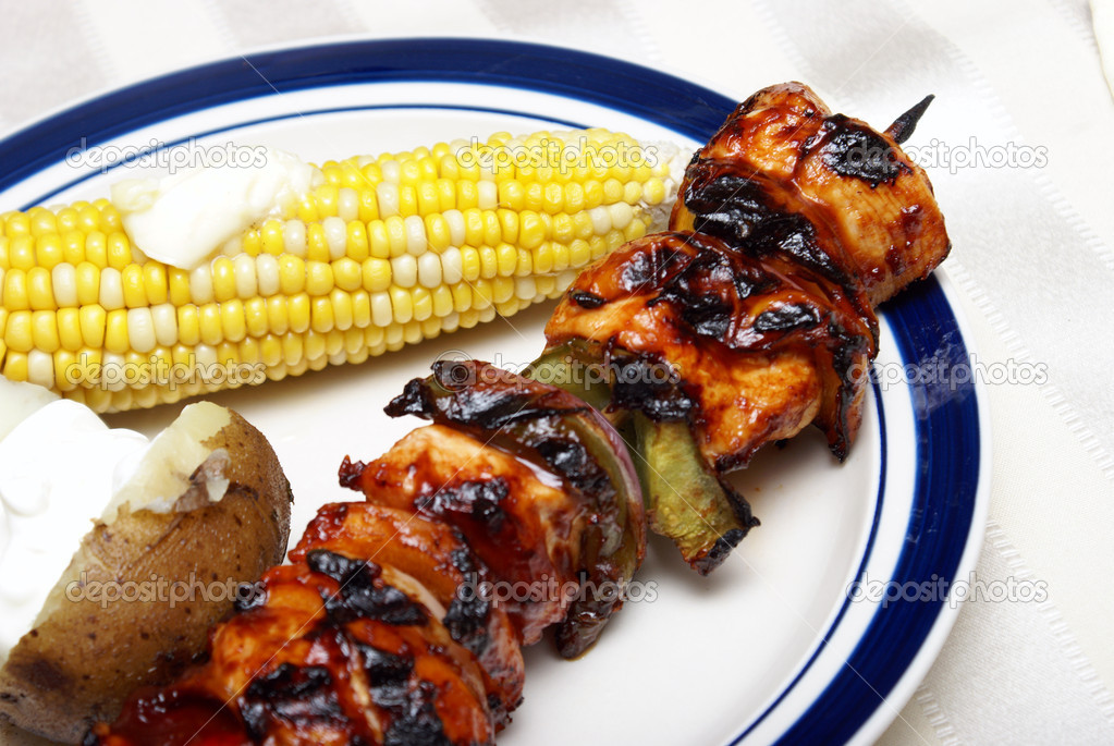 A skewer of chicken kabobs on a plate with a cob of corn and potato. — Stock Photo #8698749