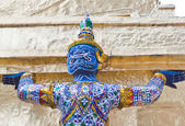 A giant blue body use two hands carrying a pagoda base — Stock Photo