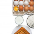 Raw eggs, glass of milk, flour and baked good — Stock Photo