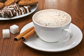 Cappuccino with cinnamon bark and sweets — Stock Photo