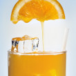 Stock Photo: Orange juice is flowing in glass with ice