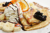 Pancakes with cheese, cream, banana, chocolate... — Stock Photo