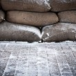 Stock Photo: Old brown sandbags on snow covered wooden floor